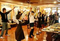 昼食時にレストランで軽快なリズムのダンスを披露する高校生達